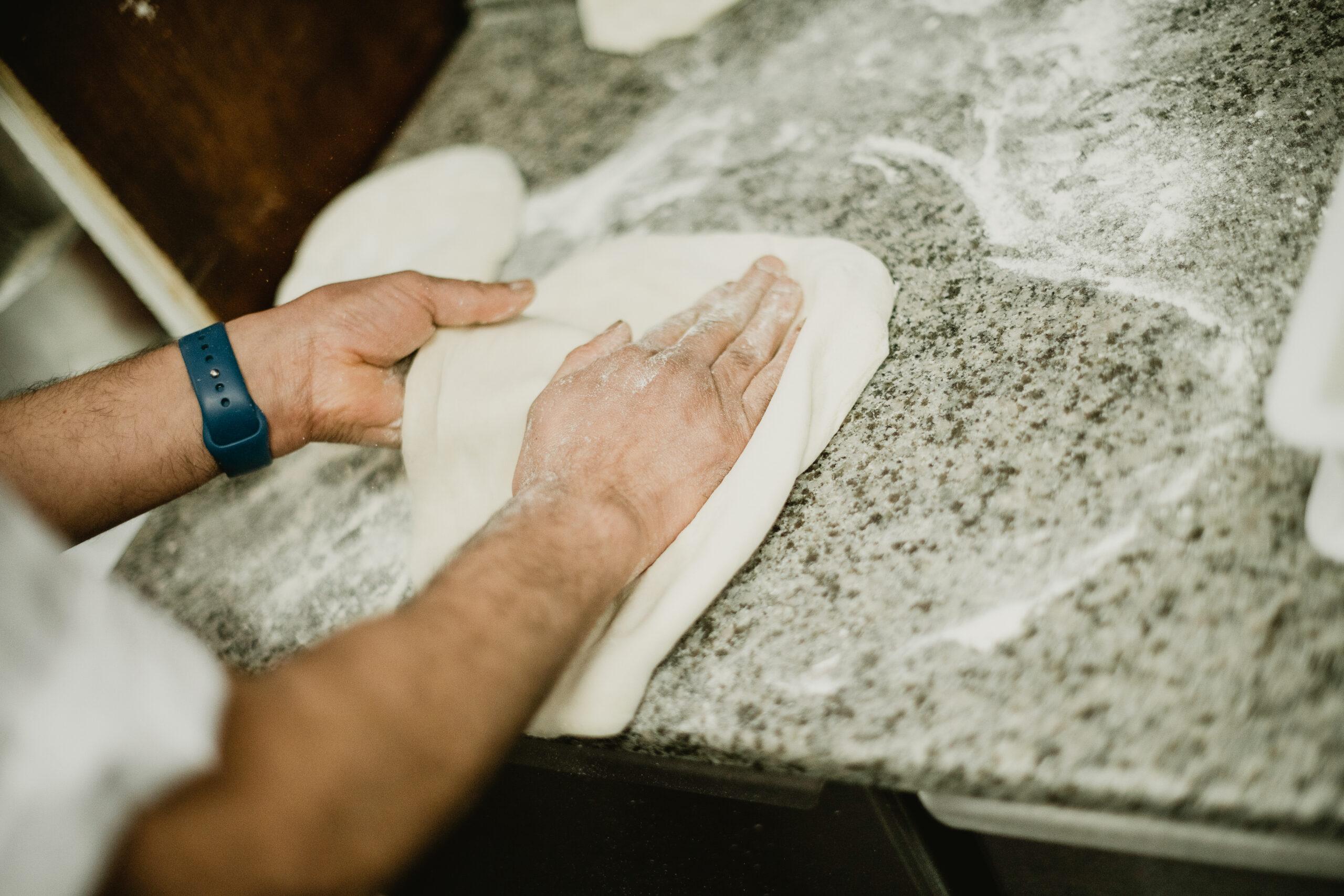 Rolling out Pizzeria Villaggio pizza dough